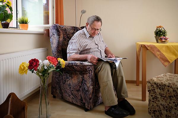 Mann sitz in Sessel und liest